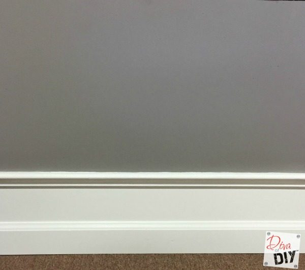 Cheap and easy Home Improvement DIY to add drama to builder grade baseboards by adding trim to your walls and painting the space between them.